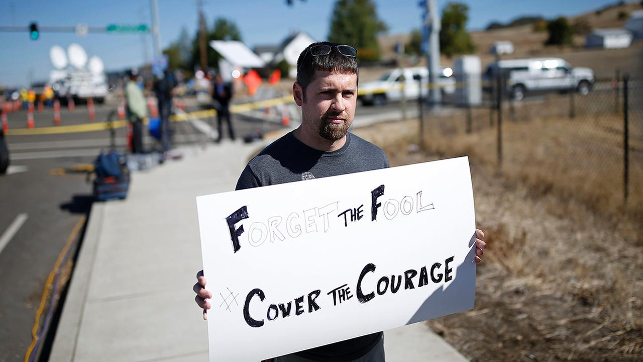 Mike Scott holds up a sign near the road that leads to Umpqua Community College Friday, Oct. 2, 2015, in Roseburg, Ore.