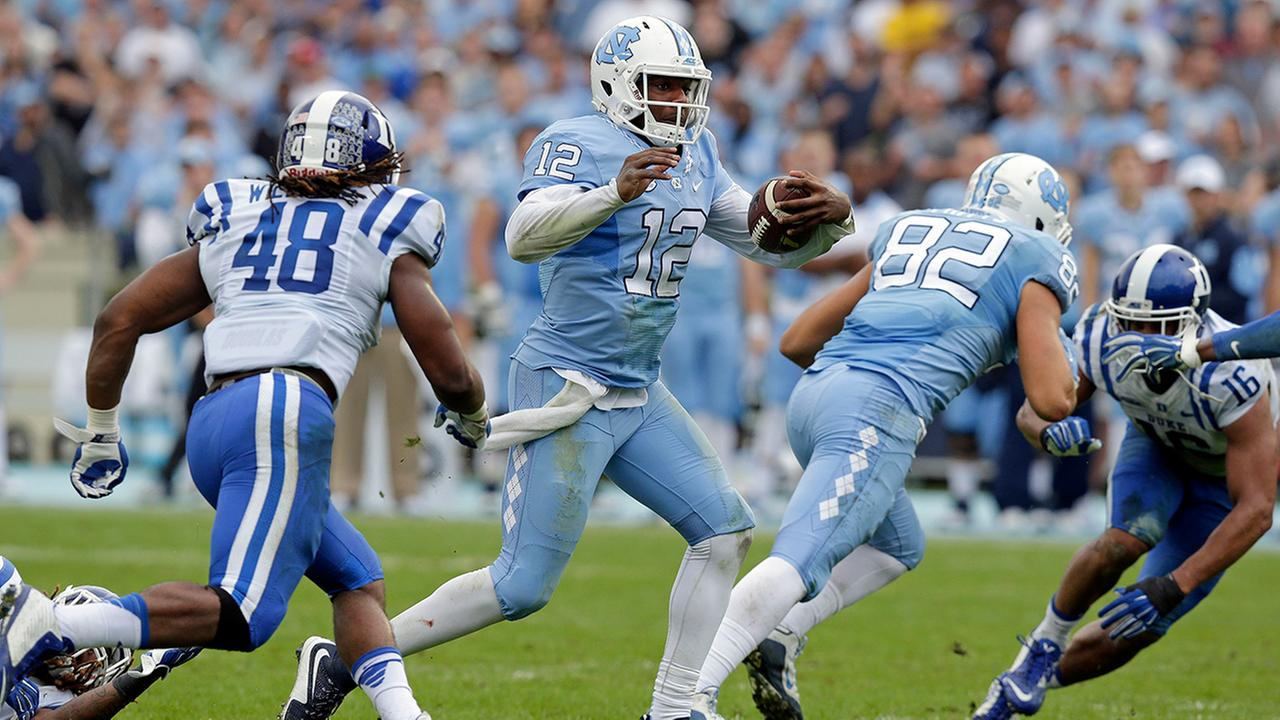 North Carolina quarterback Marquise Williams (12) finds some running room as Dukes Deion Williams (48) looks for the tackle during the first half