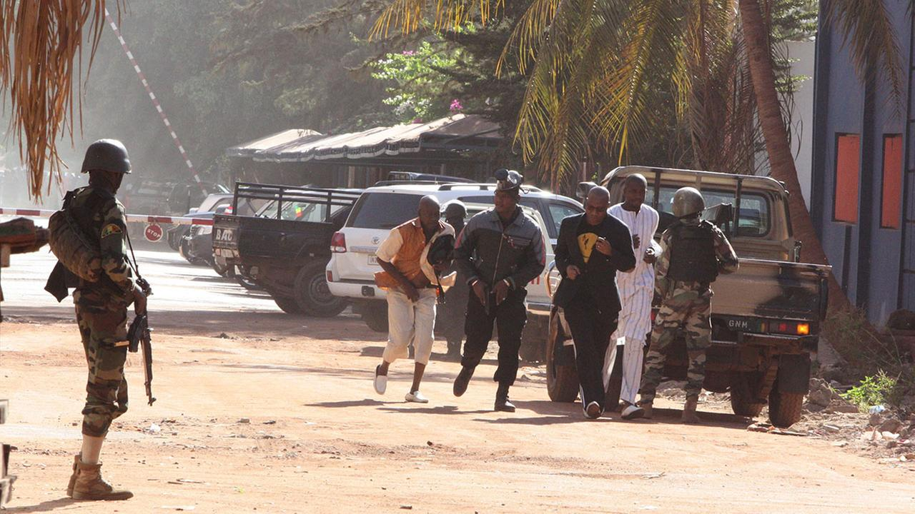 People run to flee from the Radisson Blu Hotel in Bamako, Mali, Friday, Nov. 20, 2015.