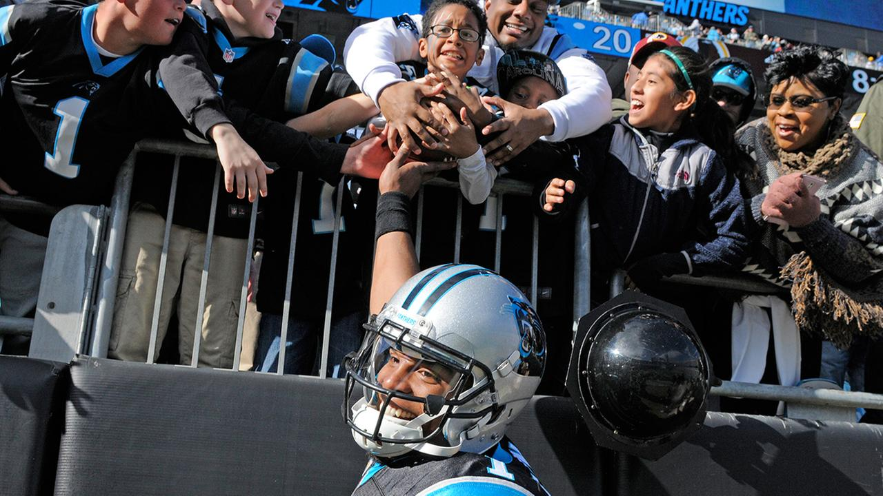 Carolina Panthers Cam Newton hands a touchdown ball to a fan in the first half of an NFL football game against the Washington Redskins in Charlotte, N.C., Sunday, Nov. 22, 2015.