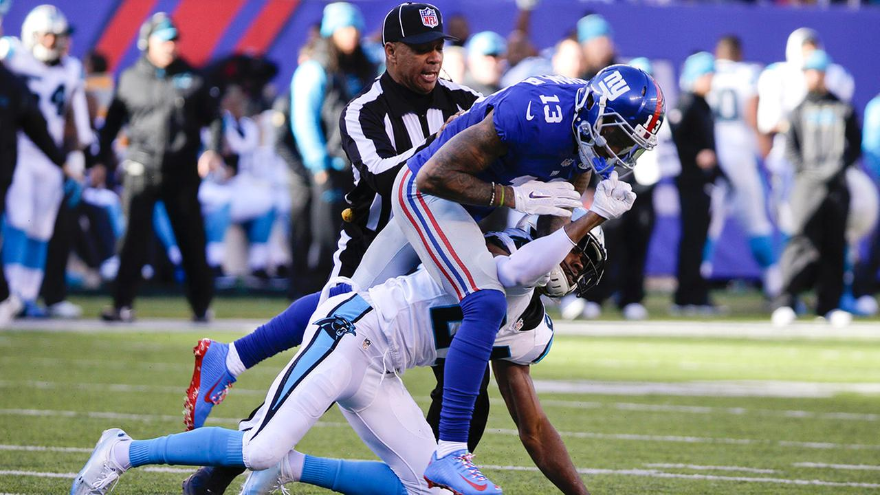 A referee separates New York Giants wide receiver Odell Beckham (13) and Carolina Panthers Josh Norman (24) during the first half of an NFL football game Sunday, Dec. 20, 2015