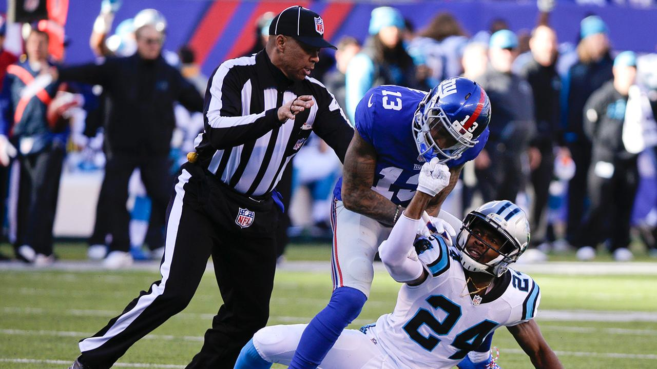 A referee, left, separates New York Giants wide receiver Odell Beckham (13) and Carolina Panthers Josh Norman (24) during the first half of an NFL football game Sunday, Dec. 20