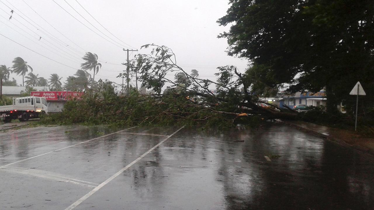 A tree blocks a road after it was blown down by the encroaching cyclone Winston in Nakasi, Fiji, Saturday, Feb. 20, 2016. The Pacific island nation of Fiji is hunkering down as a formidable cyclone with winds of 300 kilometers per hour approac