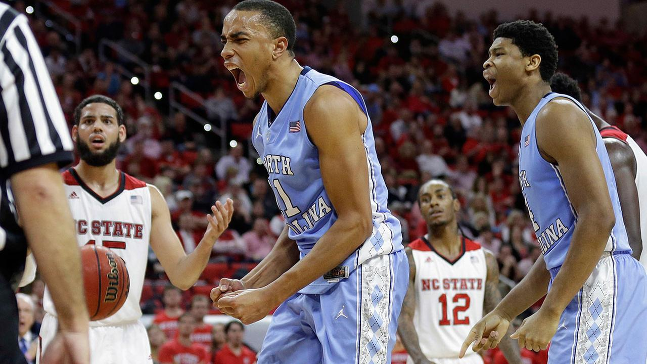 North Carolinas Brice Johnson, center, and Isaiah Hicks, right, react following a play as North Carolina States Cody Martin looks on at left