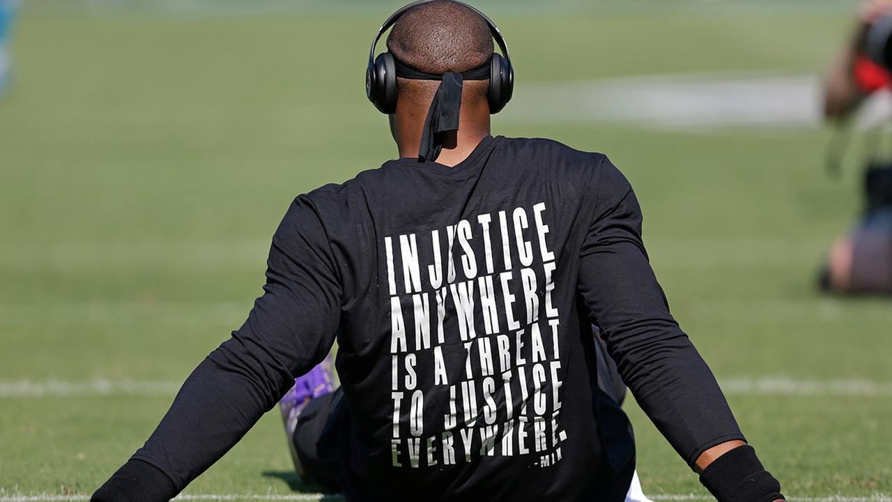 Carolina Panthers Cam Newton wears a shirt with a quote by Martin Luther King as he warms up before an NFL football game against the Minnesota Vikings in Charlotte, N.C.