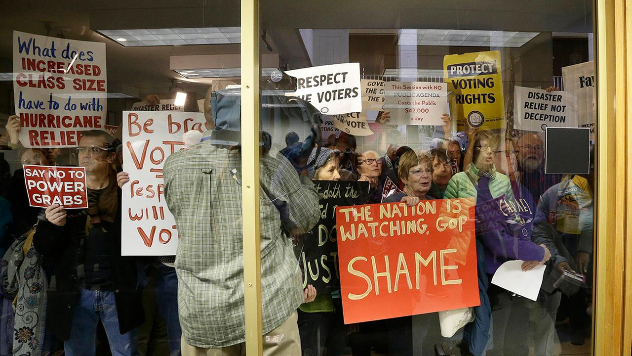 Protestors gather outside of a press conference room during a special session Thursday.
