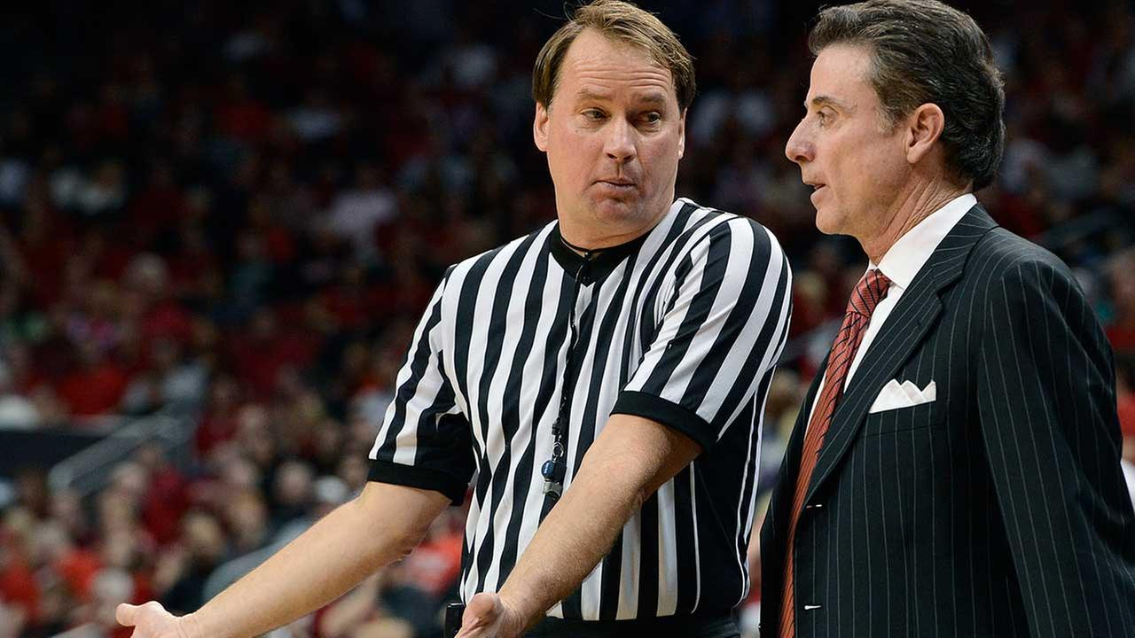 Referee John Higgins, center, explains a call to Louisville head coach Rick Pitino Thursday, Feb. 14, 2013.