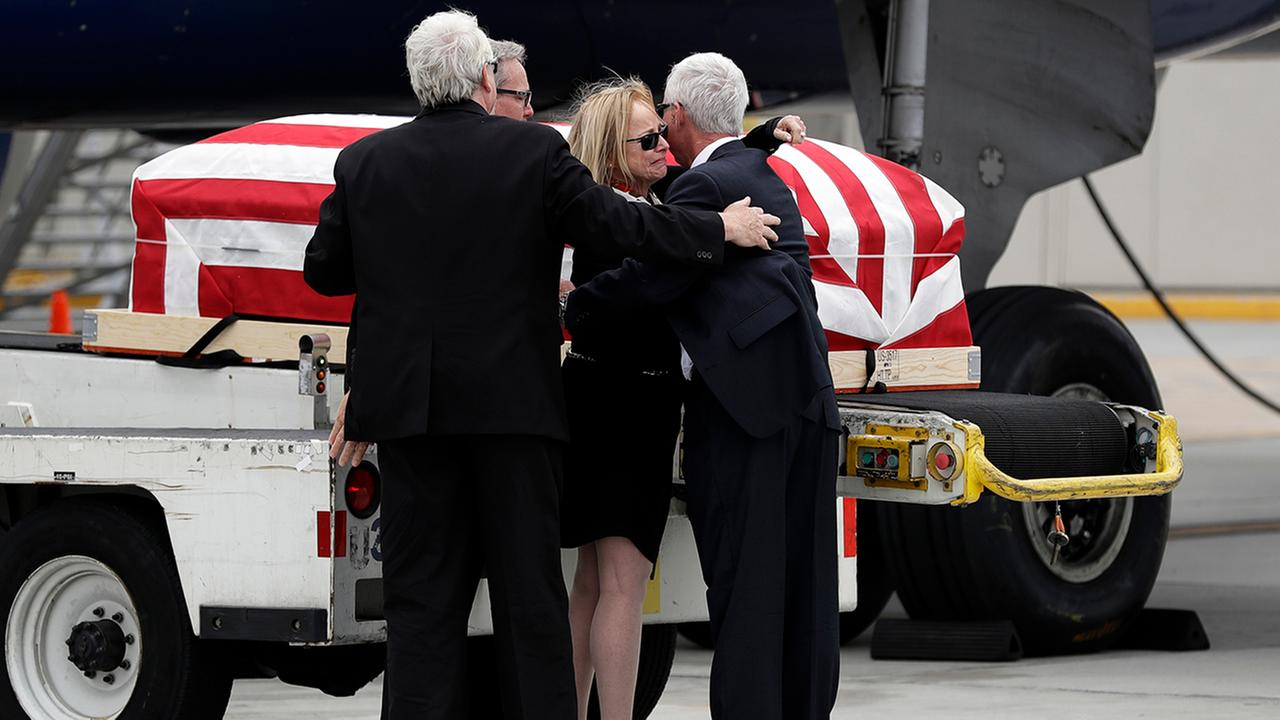 Deborah Crosby, center right, hugs her brother John Crosby, right, in front of her fathers casket after its arrival to the airport Friday, May 26, 2017, in San Diego.