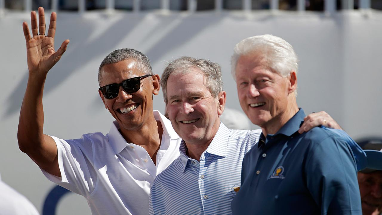 Former Presidents Barack Obama, George Bush and Bill Clinton greet spectators on the first tee at the Presidents Cup at Liberty National Golf Club in Jersey City, N.J.,