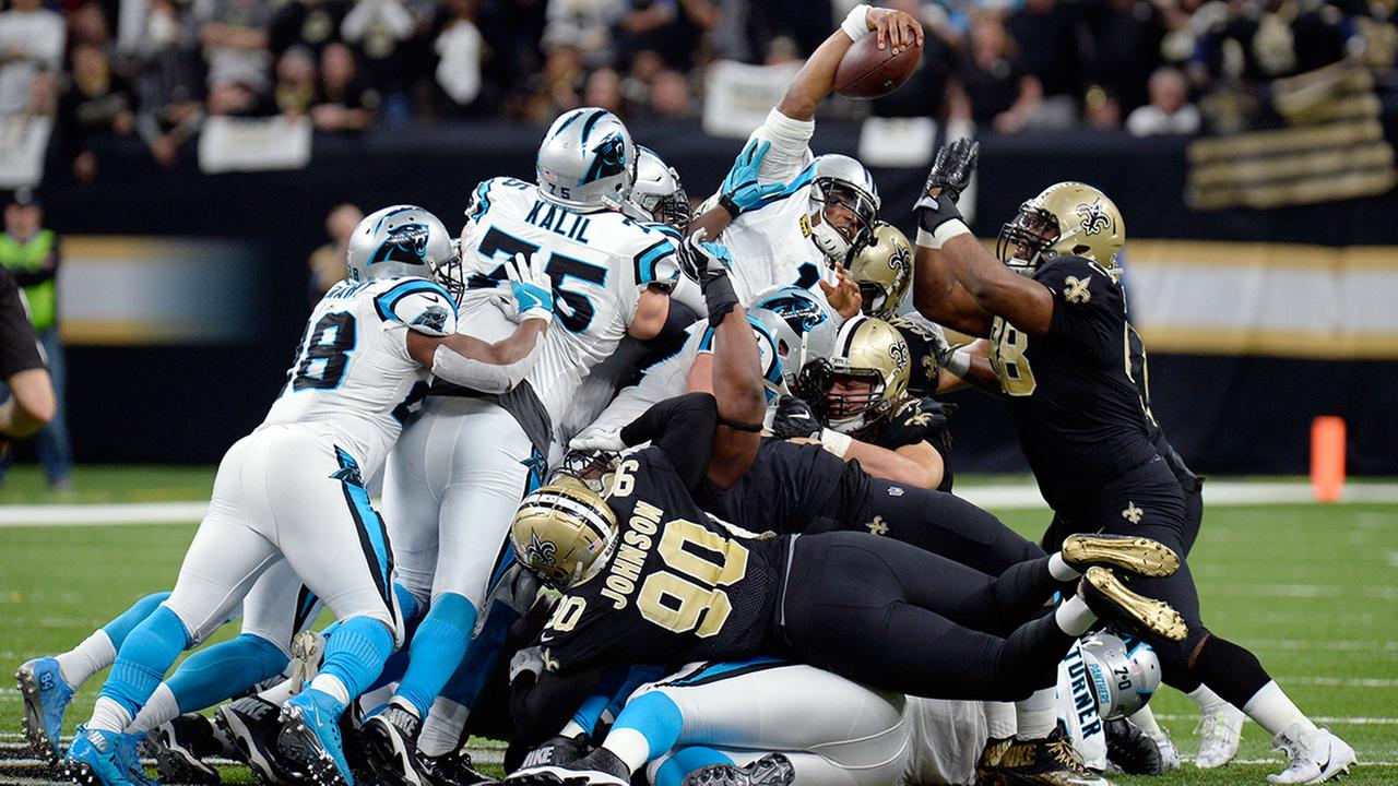 Carolina Panthers quarterback Cam Newton reaches over the pile for a first down in the first half of against the New Orleans Saints in New Orleans, Sunday, Jan. 7, 2018.