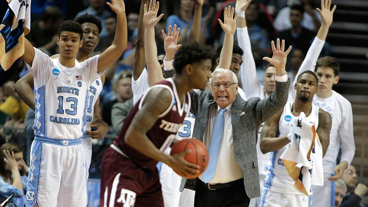 North Carolina head coach Roy Williams, center, and players on the bench raise their arms as Texas A&Ms Jay Jay Chandler (0) looks to shoot.
