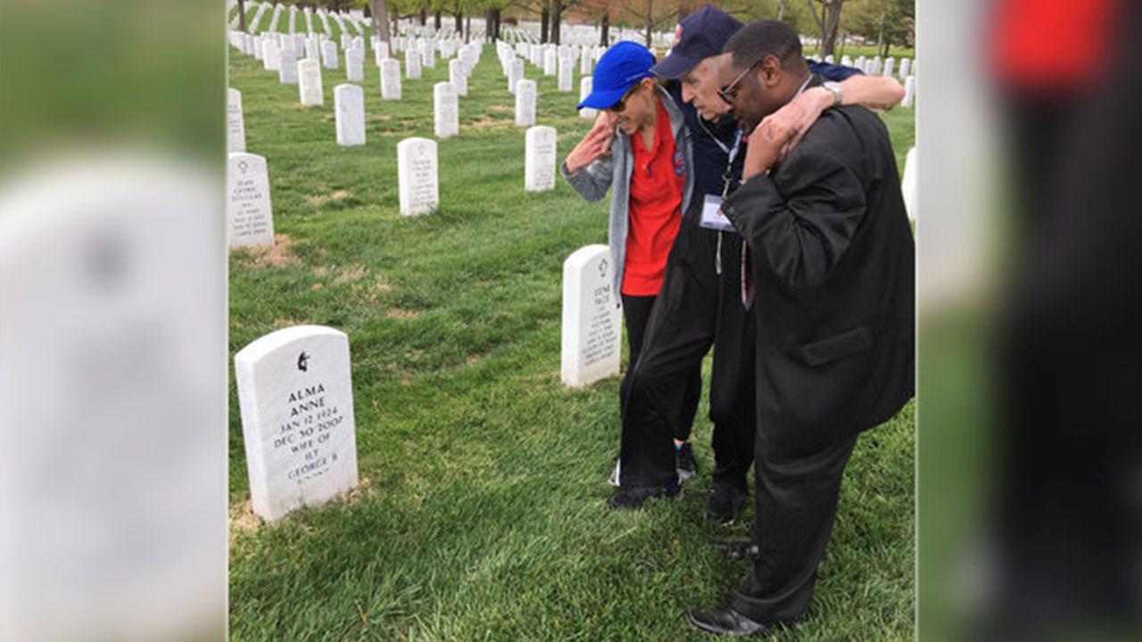 Volunteers help WWII veteran to his wifes grave