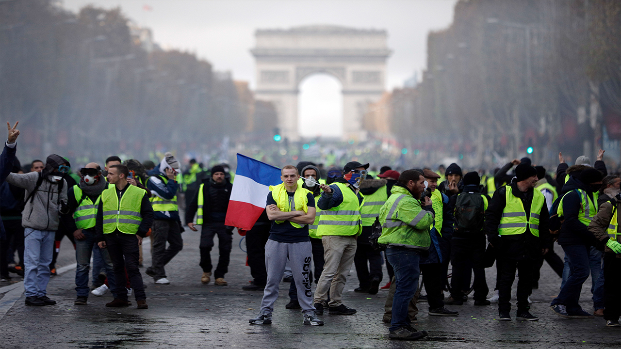 Demonstrators, called the yellow jackets, march on the famed Champs-Elysees avenue in Paris, France, as they protest against the rising of the fuel prices, Saturday, Nov. 24, 2018.