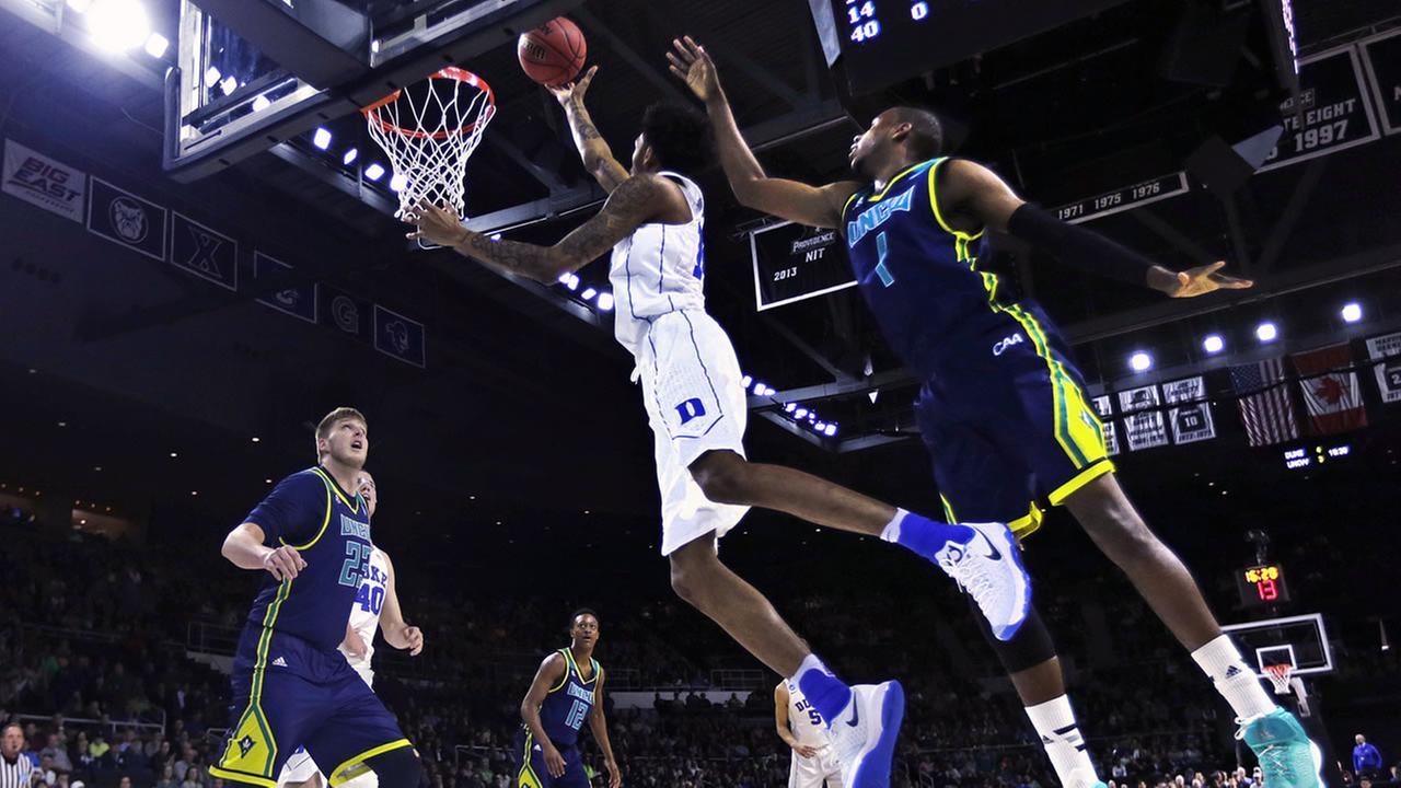 Duke guard Brandon Ingram, center, drives to the basket past North Carolina-Wilmington guard Chris Flemmings
