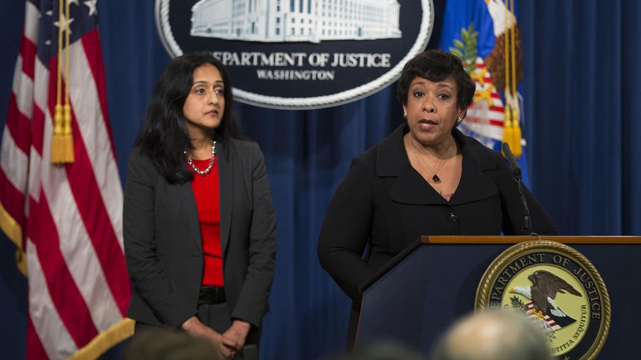 Vanita Gupta, head of the Justice Departments civil rights division listens at left as Attorney General Loretta Lynch speaks