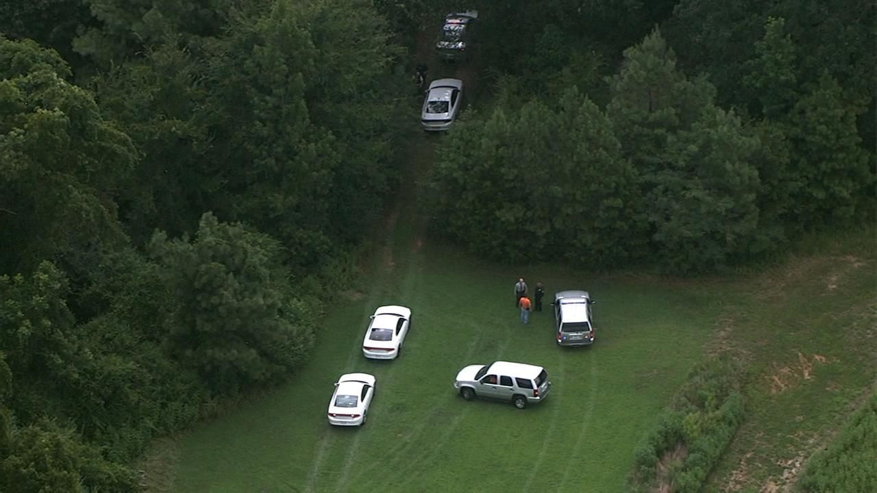 Officers searching a wooded area for Hicks.