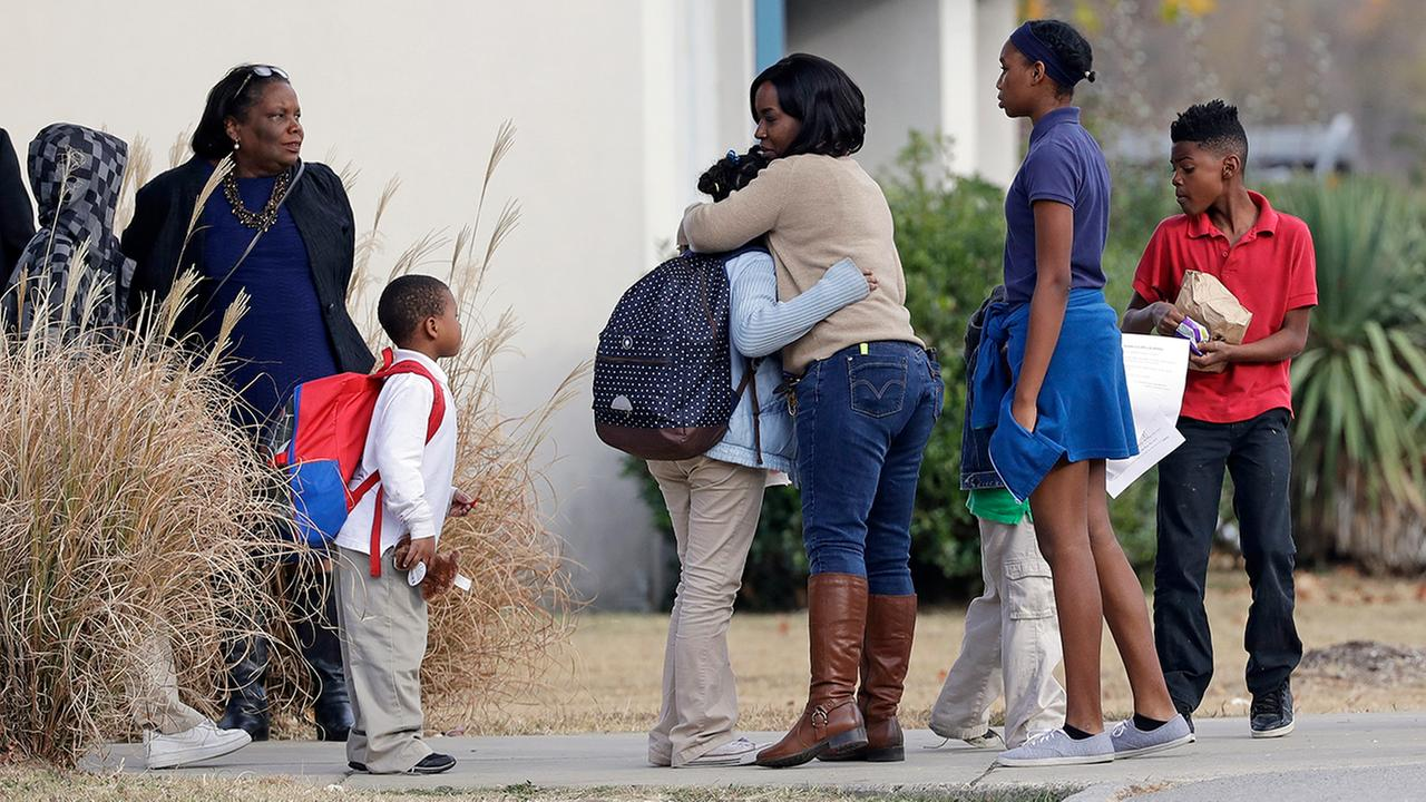 A child gets a hug as students wait for their rides home outside Woodmore Elementary School Tuesday, Nov. 22, 2016, in Chattanooga, Tenn.