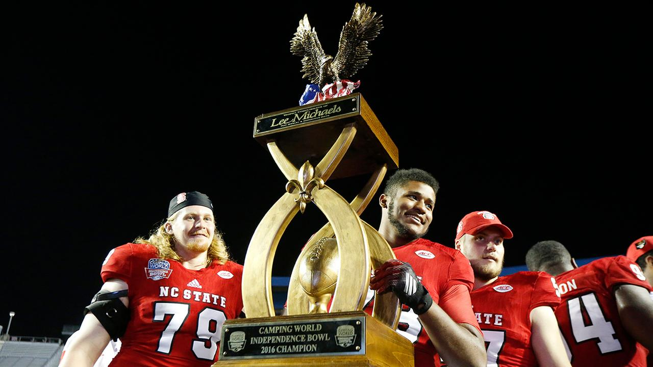 N.C. State players hoist the trophy after winning the Independence Bowl over Vanderbilt.