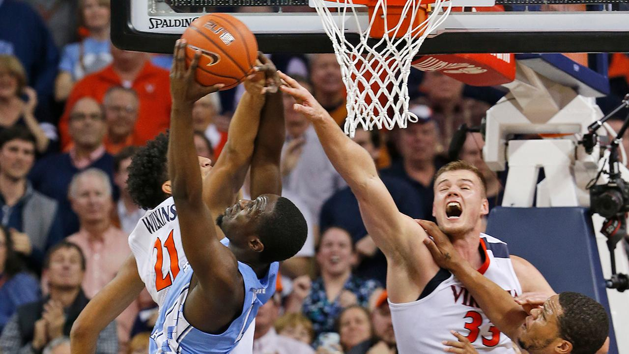 Virginia forward Isaiah Wilkins, left, and center Jack Salt block the shot of North Carolina forward Theo Pinson, one of eight Virginia blocks.