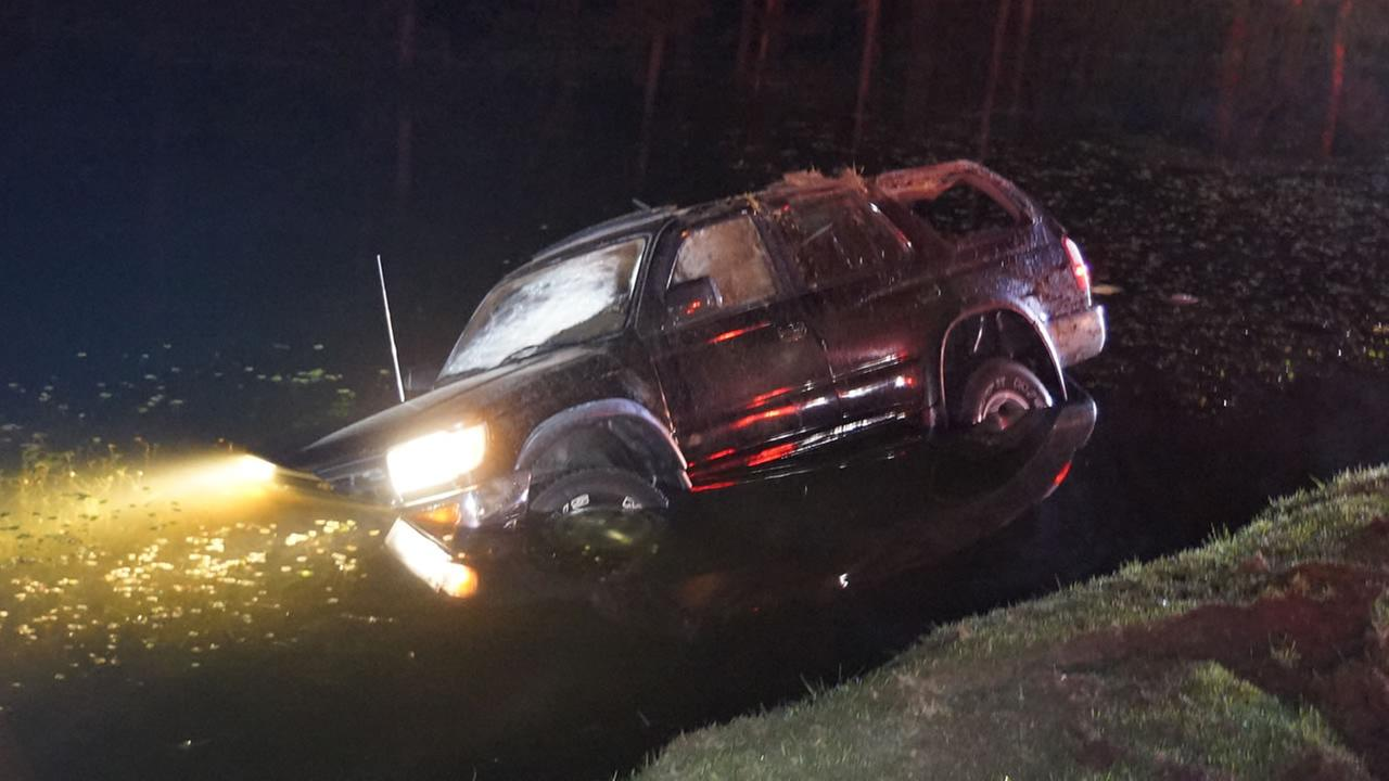 The SUV landed in shallow water near the edge of the pond.