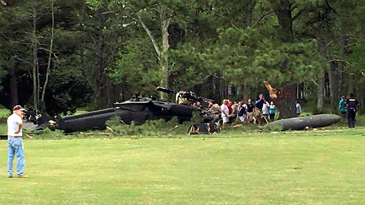 People examine an Army UH-60 helicopter from Fort Belvoir, Va., after it crashed at the Breton Bay Golf and Country Club on Monday in Leonardtown, Md.