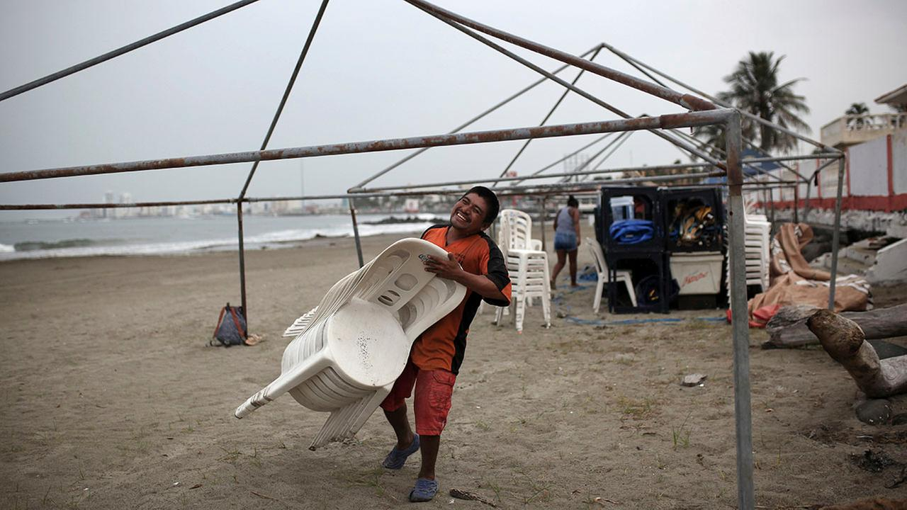 A man carries away plastic chairs as beachfront businesses strip down to their bare bones in preparation for the arrival of Tropical Storm Franklin, in Veracruz, Mexico.