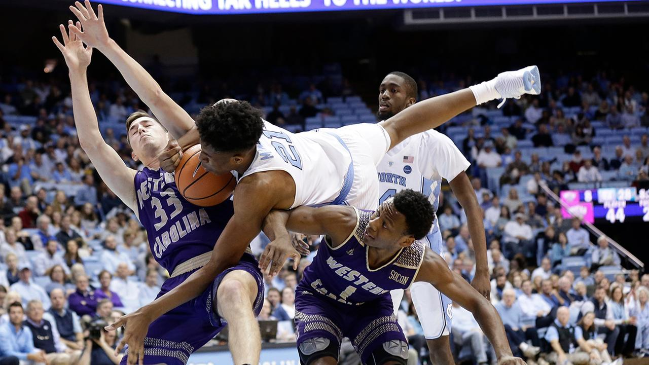 North Carolinas Sterling Manley (21) falls over Western Carolinas Onno Steger (33) and Desmond Johnson (1) during the first half in Chapel Hill on Wednesday.