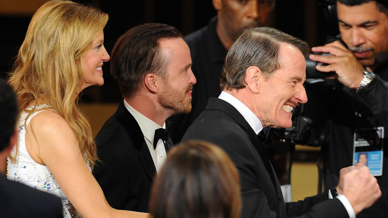 Anna Gunn, and from left, Aaron Paul and Bryan Cranston walk on stage to accept the award for outstanding drama series at the 66th Primetime Emmy Awards at the Nokia Theatre.