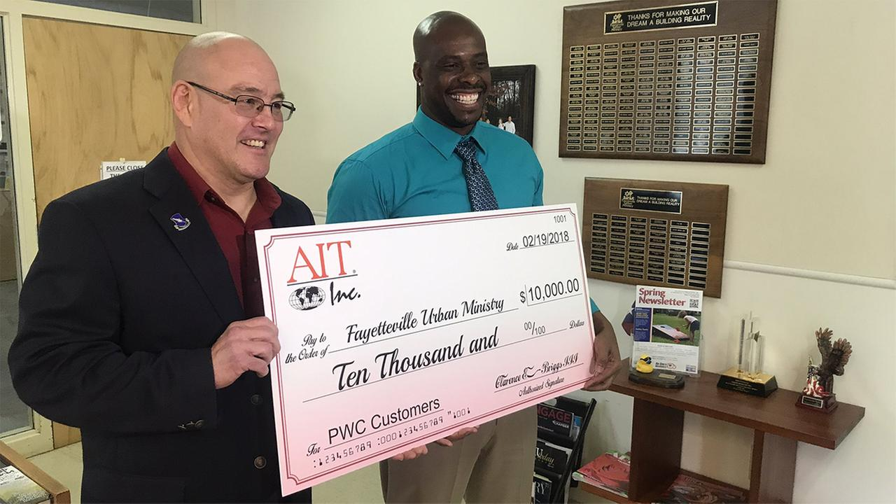 Clarence Briggs, CEO of AIT Inc., left, presents a check to Johnny Wilson with Fayetteville Urban Ministry for $10,000.