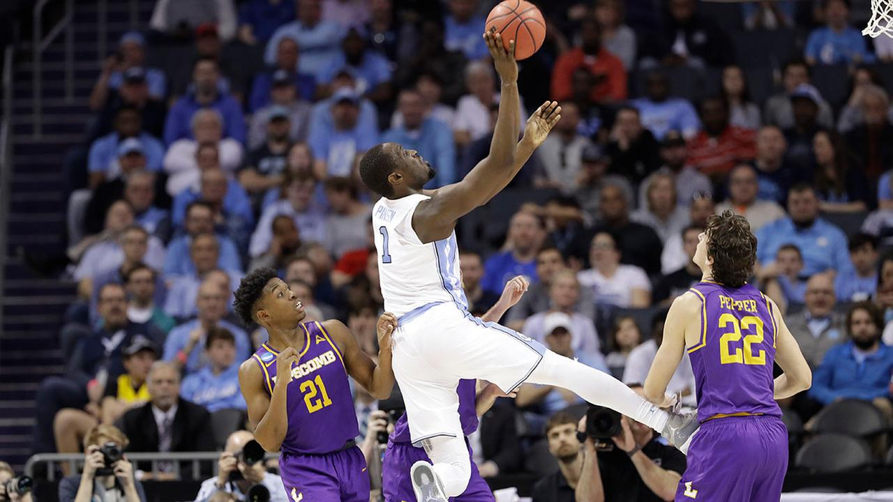 North Carolinas Theo Pinson shoots between Lipscombs Eli Pepper (22) and Kenny Cooper (21).
