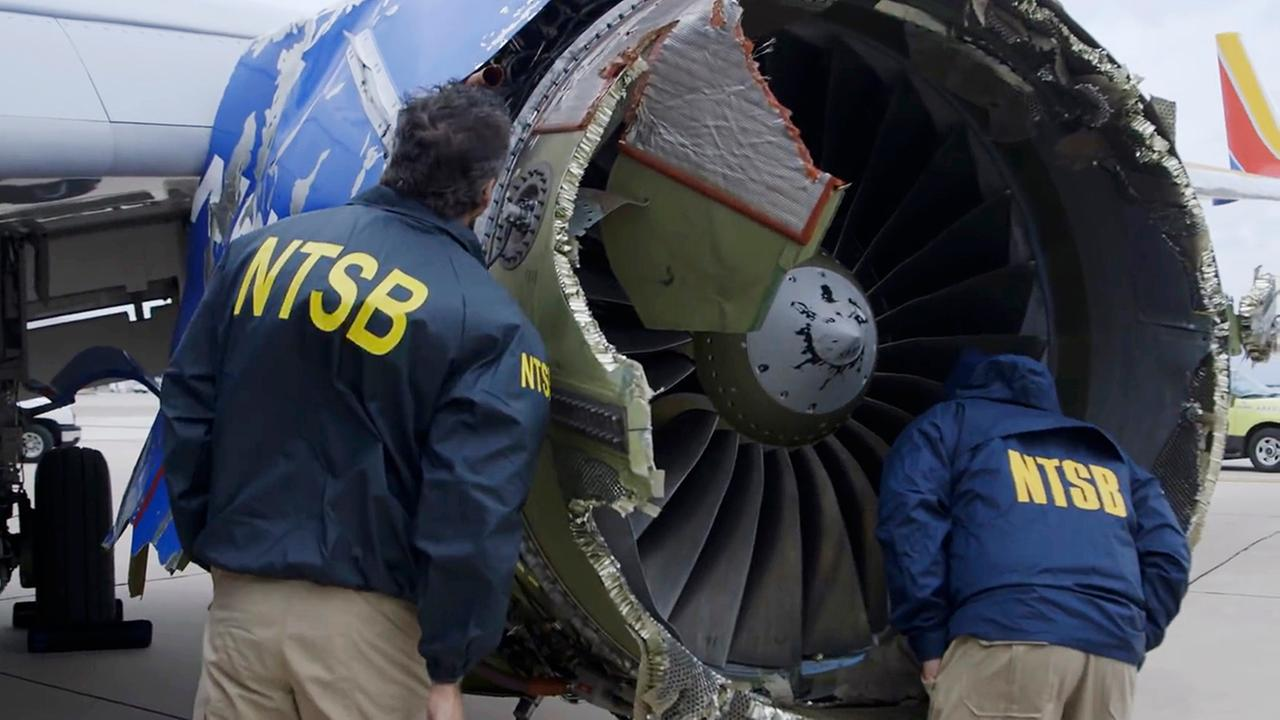In this Tuesday image, an NTSB investigator examines damage to the engine of the Southwest Airlines plane that made an emergency landing in Philadelphia.