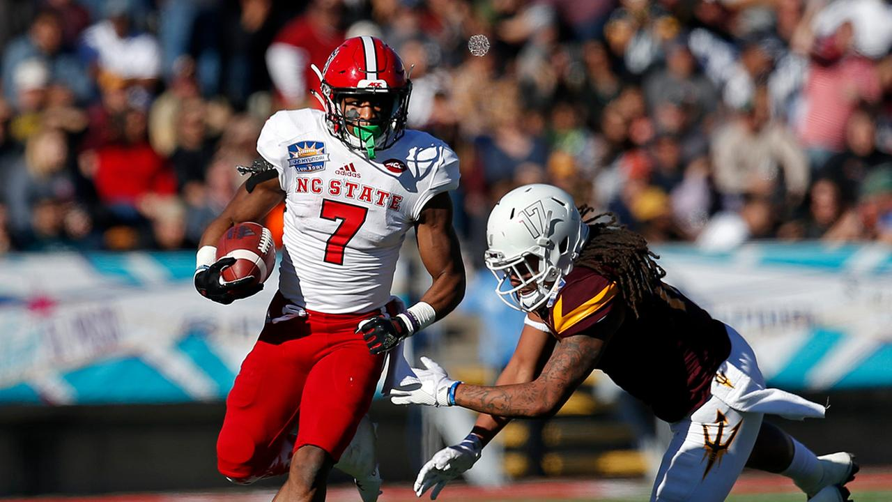 N.C. States Nyheim Hines runs away from an Arizona State defender in the Sun Bowl.