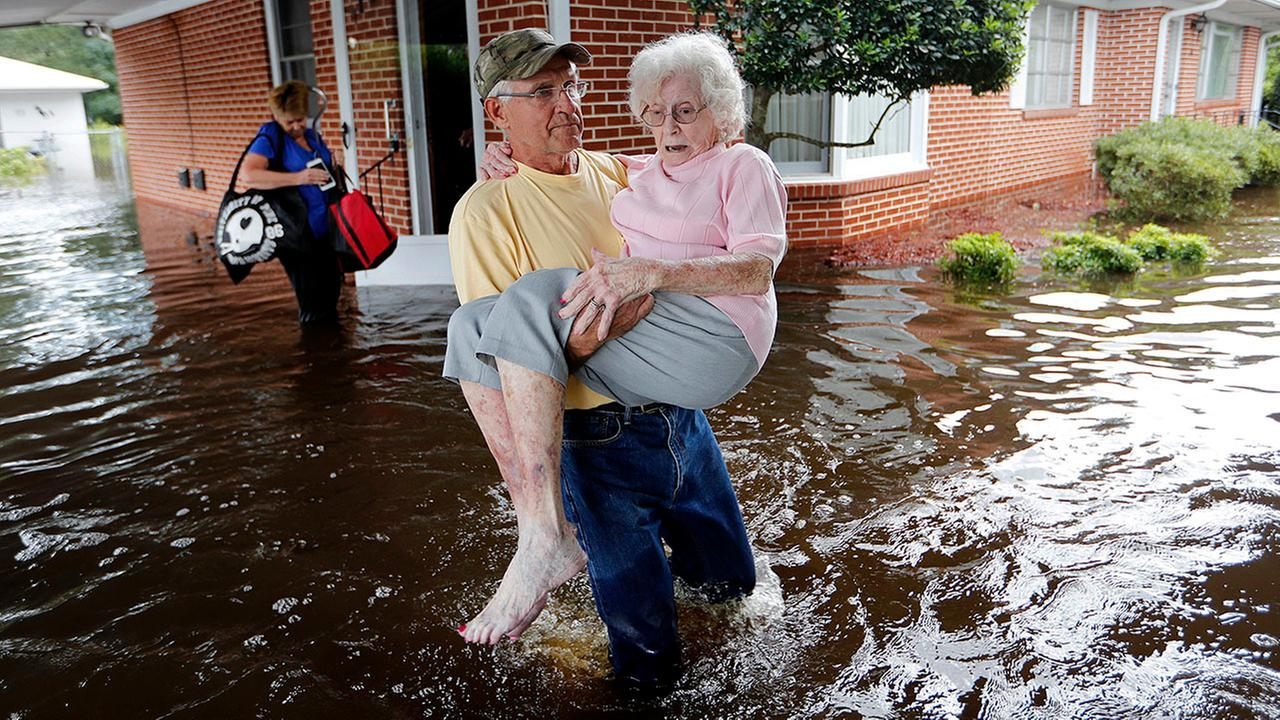 Bob Richling carries Iris Darden, 84, out of her flooded home Monday as her daughter-in-law, Pam Darden, gathers her belongings in the aftermath of Florence in Spring Lake, N.C.