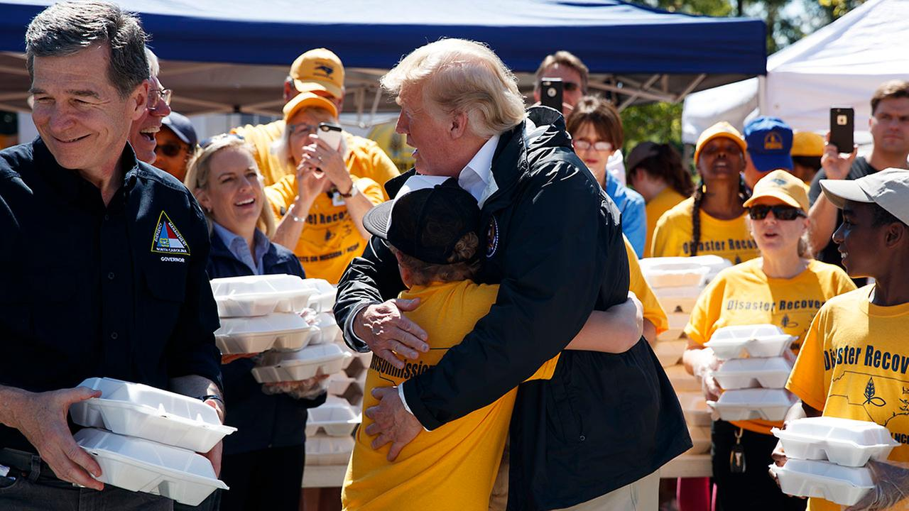 President Donald Trump hugs a young man while handing out packaged meals at Temple Baptist Church in an area impacted by Hurricane Florence, Wednesday in New Bern.