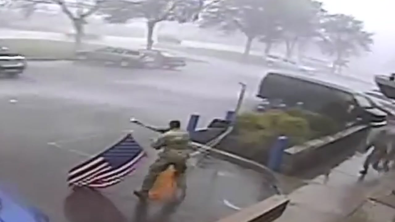 Video captures soldiers protecting the flag during severe weather in Michigan