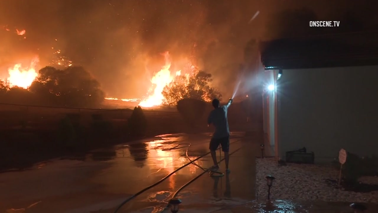 Intense video captured several men in Lake Elsinore trying to battle a massive wildfire with a garden hose.