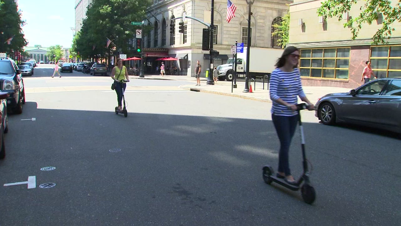 Riders on electric scooters are zooming past pedestrians on the sidewalk.