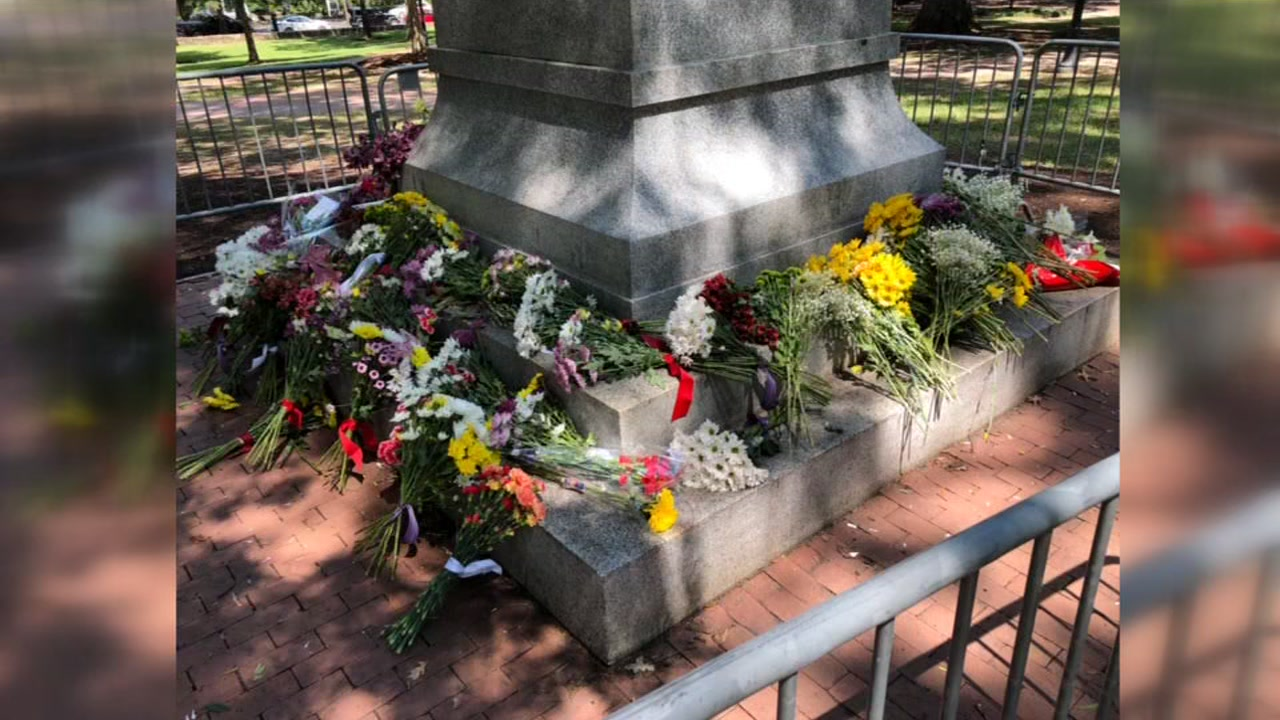 NC Sons of Confederate Veterans place flowers at base of Silent Sam monument