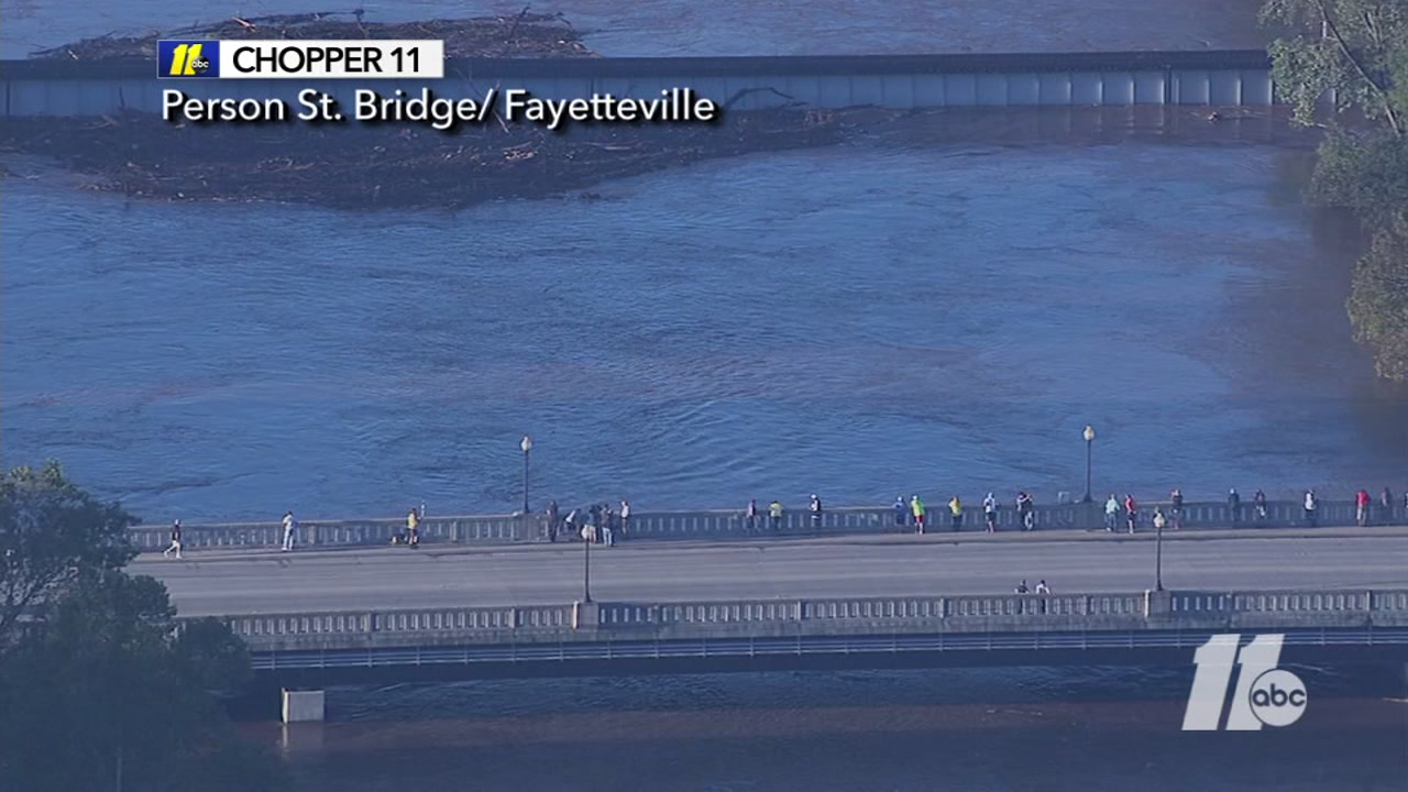 Onlookers keeping an eye on the rising Cape Fear River at the Person Street bridge.