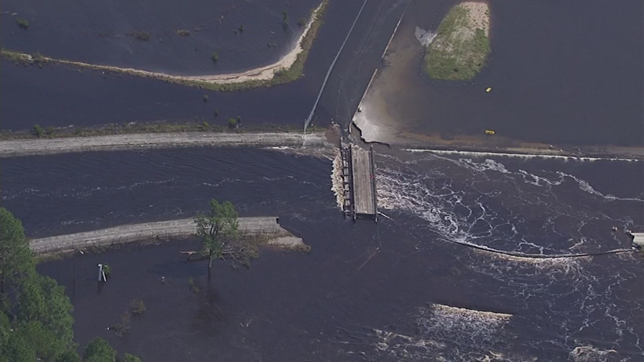 A dam containing a large lake at a NC power plant has been breached by floodwaters, and coal  might be flowing into the Cape Fear River.