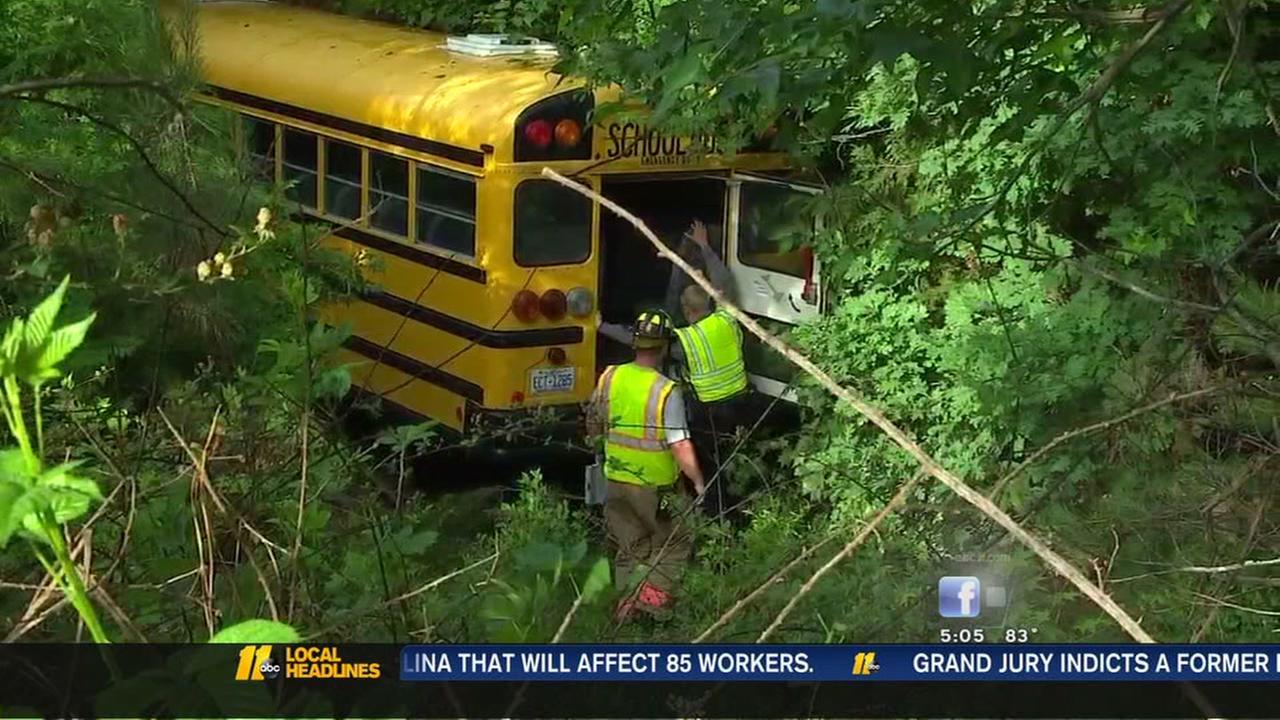 School bus crashes into woods
