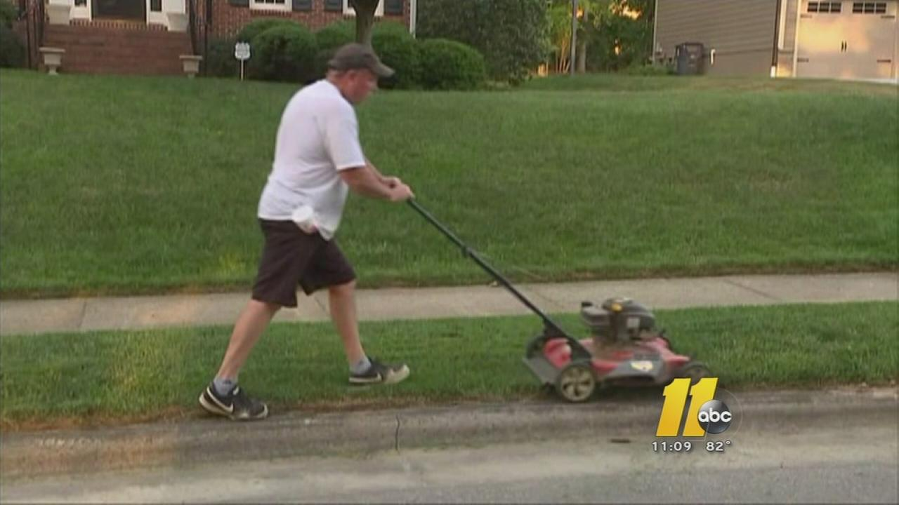 Cary council approves new noise ordinance -- man pushing lawn mower