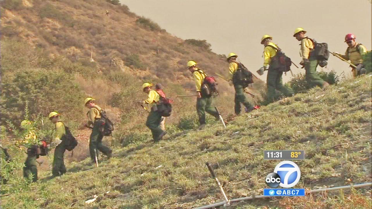 Firefighters work to put out a wildfire in the Angeles National Forest near Azusa on Tuesday, Sept. 24, 2013.