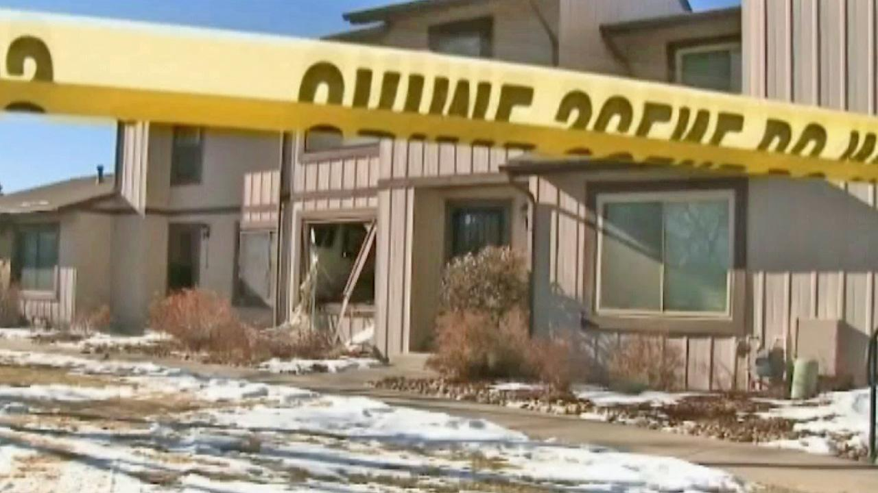 A blown-out window is seen at an Aurora, Colo. townhome where SWAT officer shot and killed a man who was holed up inside the home for hours on Saturday, Jan. 5, 2013. Police say three other people were also found dead inside the home.