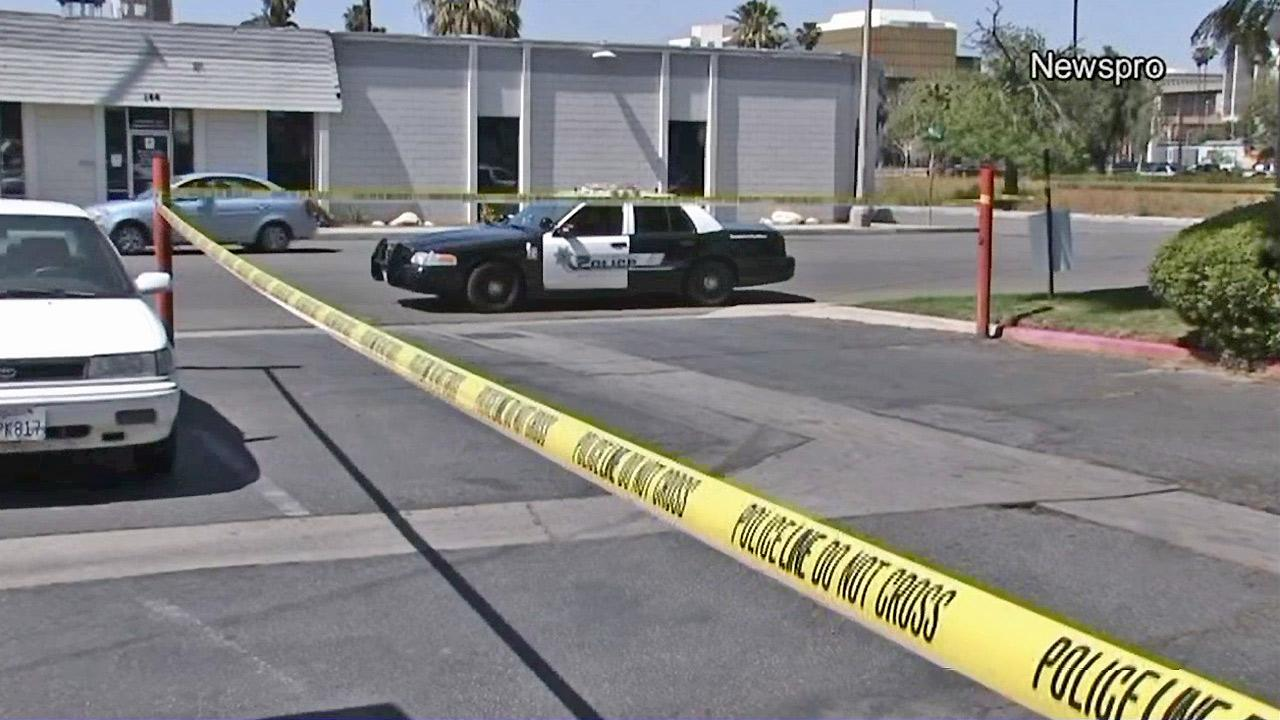 Police are seen in a parking lot where a man was shot and killed in San Bernardino on Sunday, March 24, 2013.