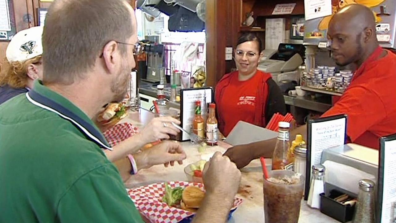 Restaurant employees serve customers in this undated file photo.