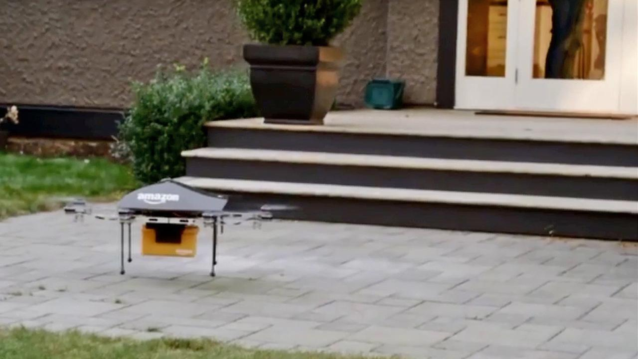 In a still from a video from Amazon, a drone delivering a package lands at the home of a customer.