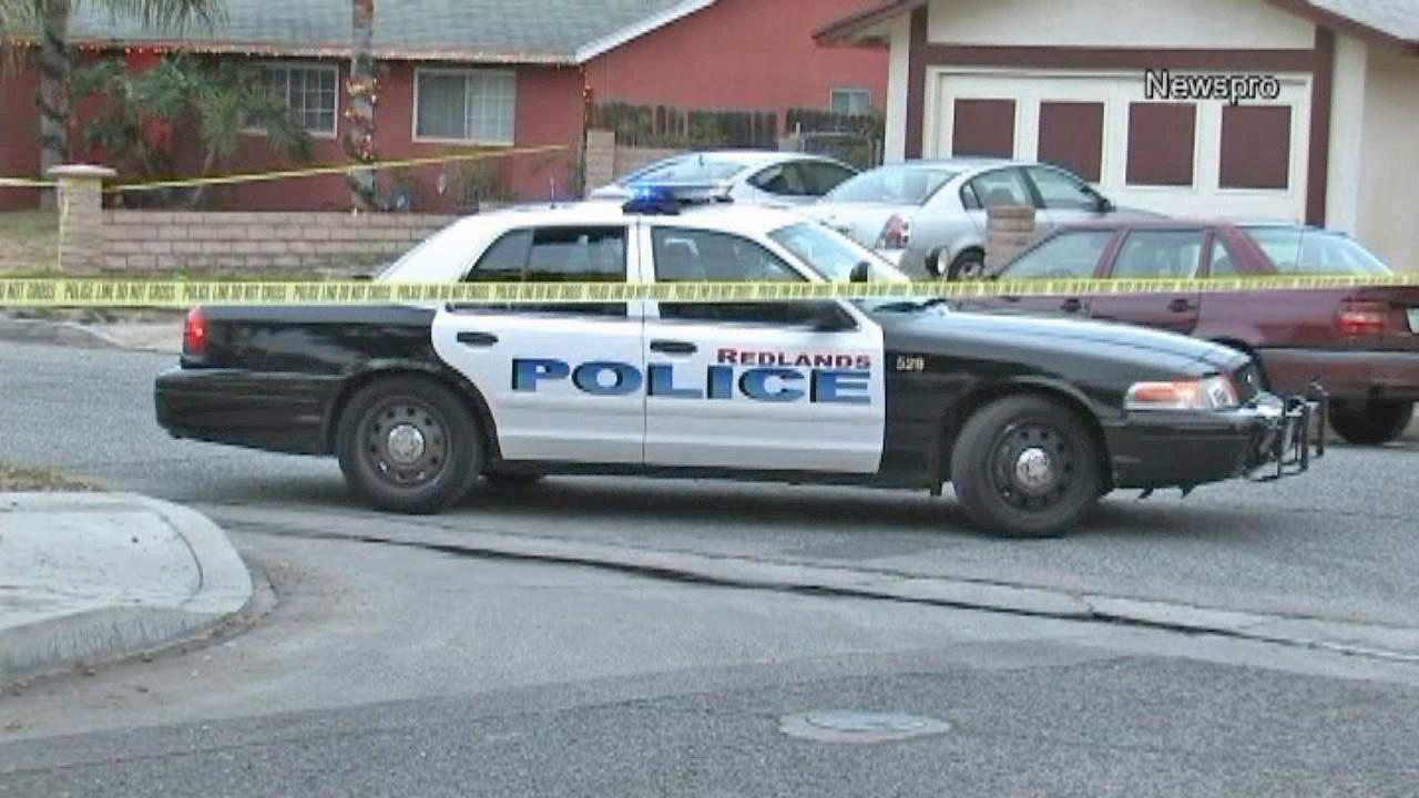 A police car is seen outside a home in Redlands where a woman was found dead and her daughter was found injured on Saturday, Dec. 28, 2013.
