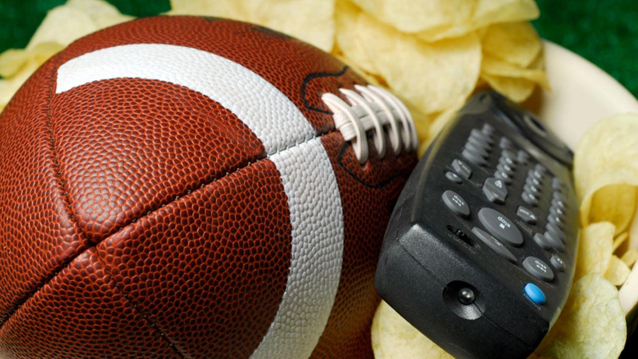 This file photo shows a football and TV remote.