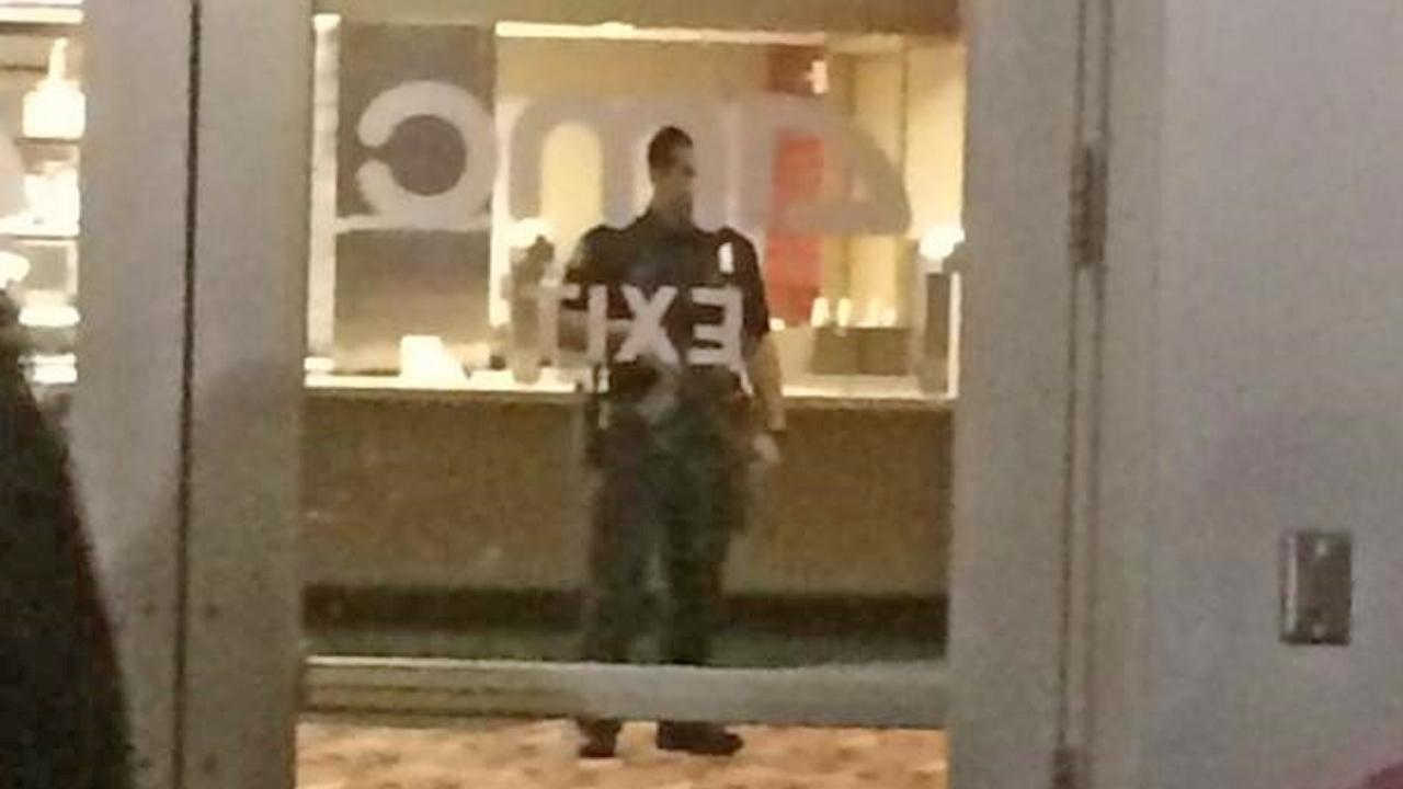 Authorities are seen inside an AMC theater in Tustin that was evacuated on Saturday, March 15, 2014.
